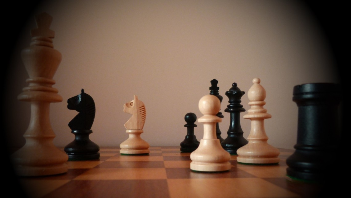 A chessboard with dark and light chess pieces on it.