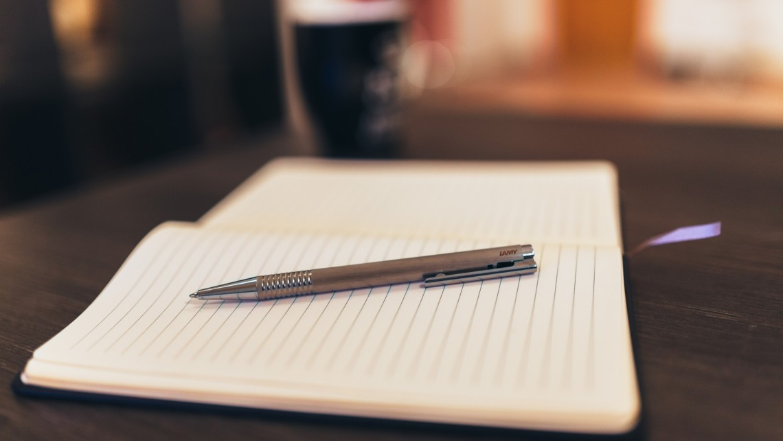 A notepad with a pen on top of it, and a black coffee cup in the background.